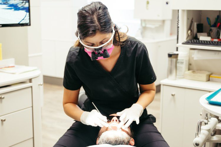 A dental assistant at New Look Dental in West Kelowna uses the Wand