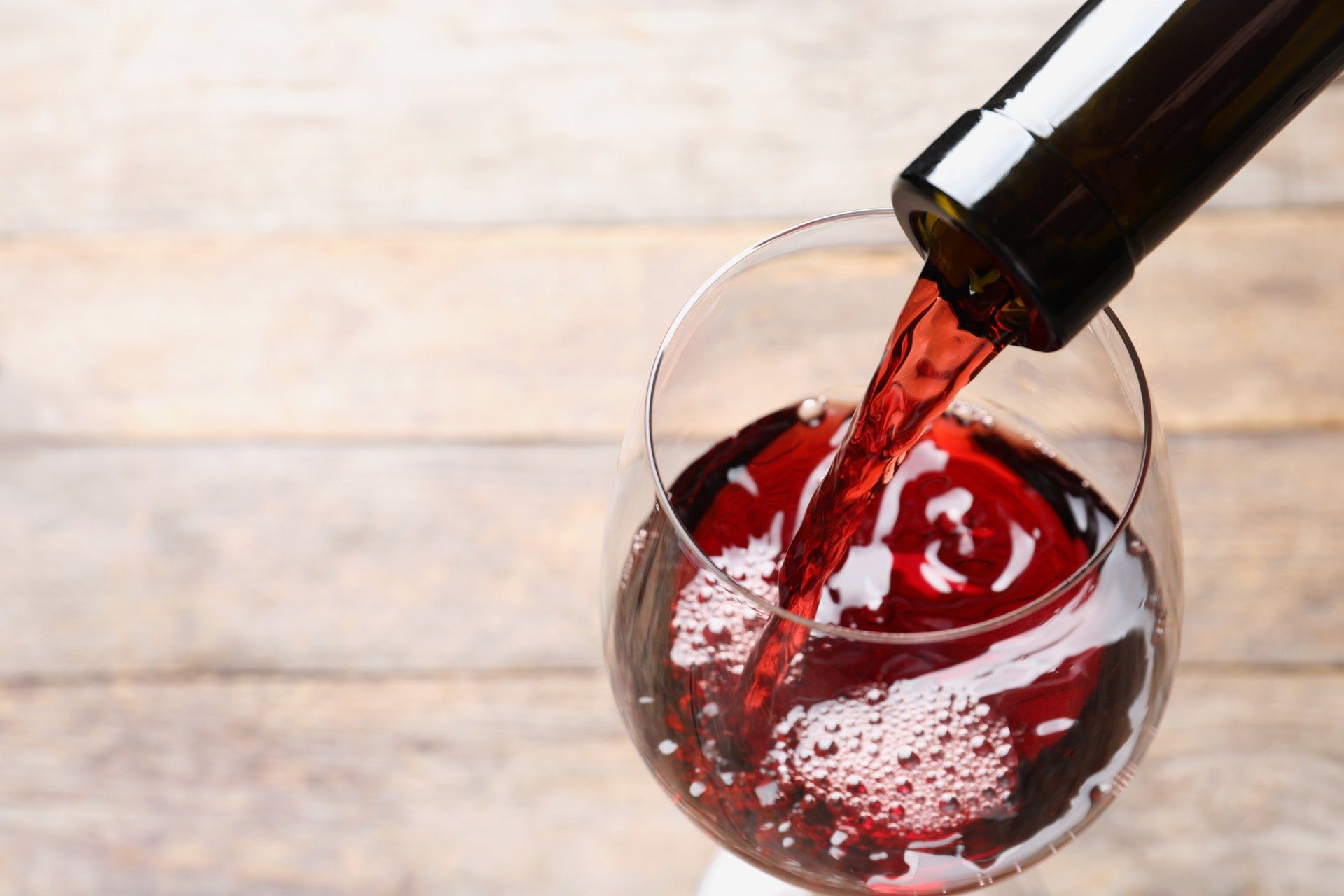 Pouring red wine from glass bottle